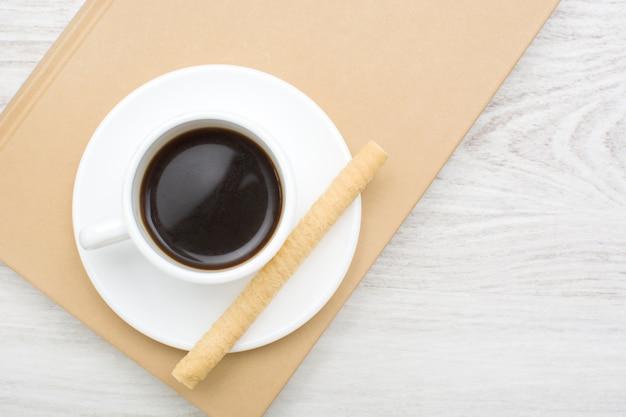 コーヒーと本と白い木製のテーブル上のウェーハ