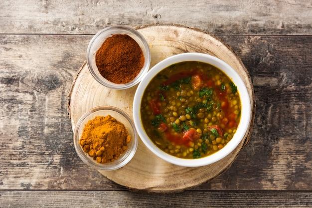 木製のテーブルの上にボウルにインドのレンズ豆のスープダル(ダル)。上面図