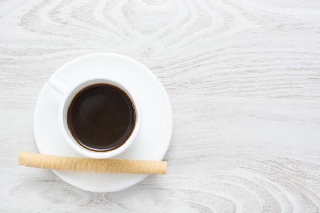 コーヒーと白い木製のテーブルコピースペースのウェーハ