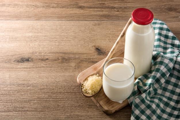Рисовое молоко в стакан и бутылка на деревянный стол