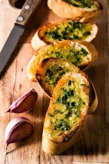 Ломтик хлеба чеснока и ингредиенты на деревянный стол
