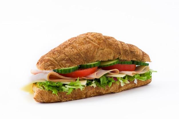 チーズ、ハム、野菜を白で隔離されるクロワッサンサンドイッチ