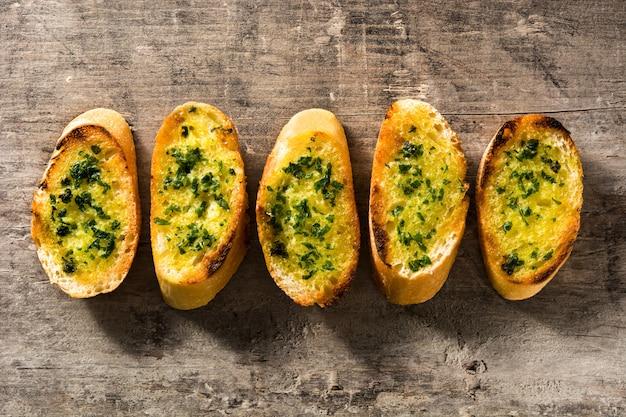 Ломтик чесночного хлеба на деревянном столе