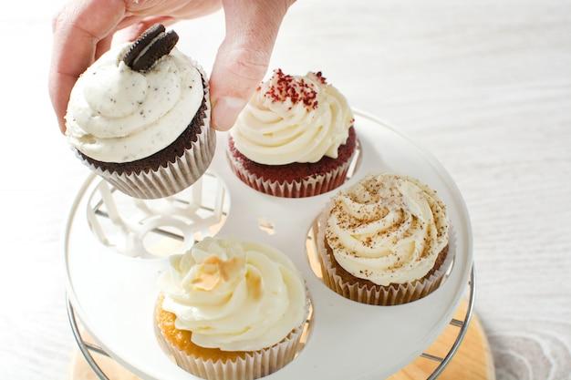 Кексы разных вкусов на белом деревянном столе