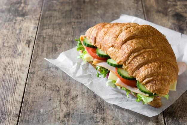 クロワッサンサンドイッチ、チーズ、ハム、野菜の木製テーブルコピースペース
