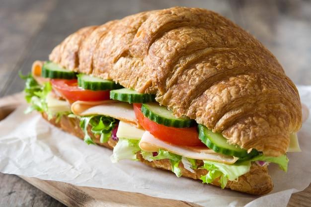 チーズ、ハム、木製のテーブルで野菜とクロワッサンサンドイッチをクローズアップ