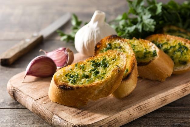 Кусок и ингридиенты хлебов чеснока на деревянном столе.