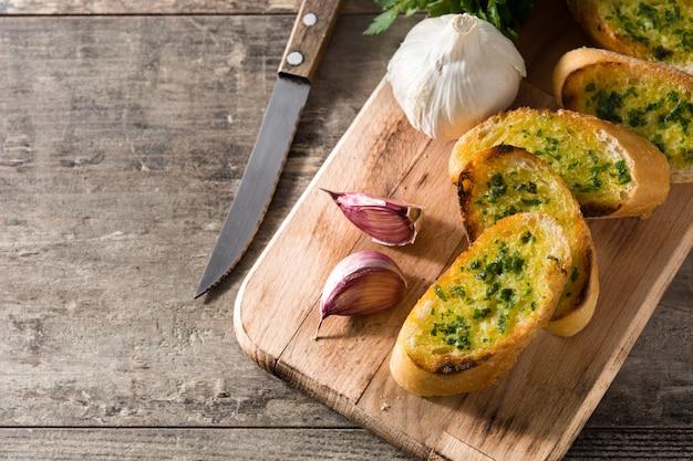Ломтик хлеба чеснока и ингредиенты на деревянный стол копией пространства