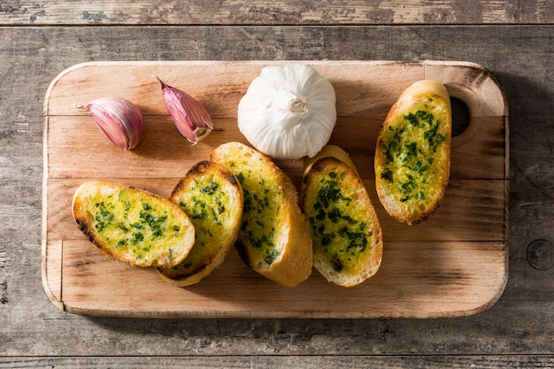 Ломтик хлеба чеснока и ингредиенты на деревянный стол, вид сверху