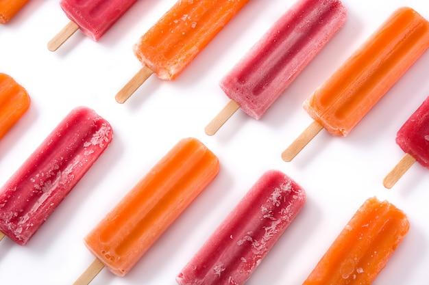 白で隔離されるオレンジとイチゴのアイスキャンディーパターン