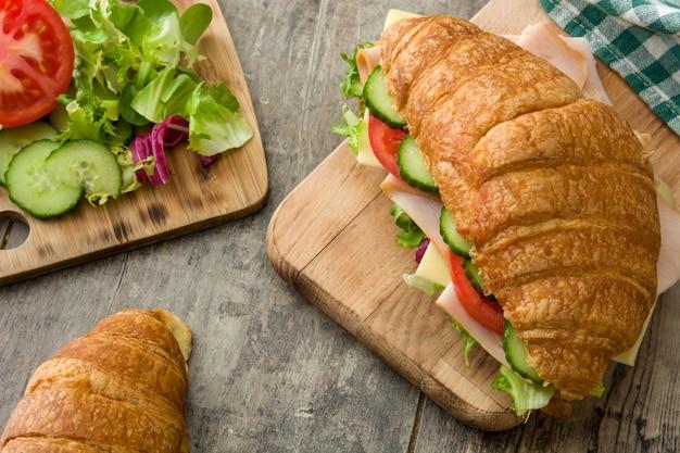 クロワッサンサンドイッチ、チーズ、ハム、野菜、木製のテーブル
