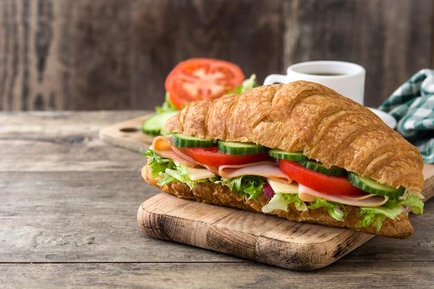 クロワッサンサンドイッチ、チーズ、ハム、野菜の木製のテーブル、コピースペース