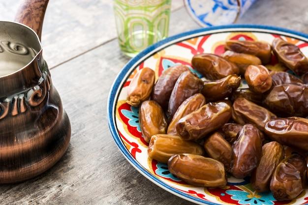 Финики еды в тарелку и чай на деревянный стол