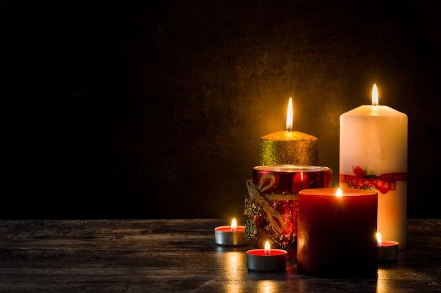 木製テーブルの上のクリスマスキャンドル。薄暗い光。