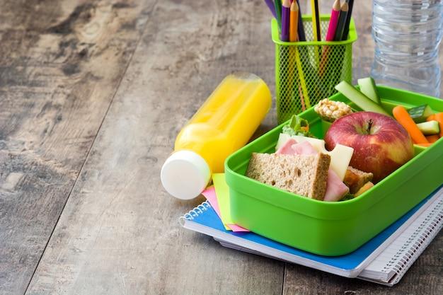 Сэндвич, овощи, фрукты и сок на деревянном столе копией пространства