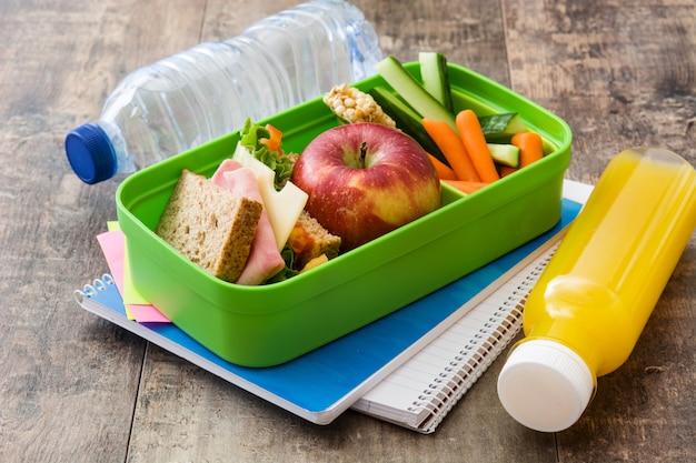 Бутерброд, овощи, фрукты и сок на деревянный стол
