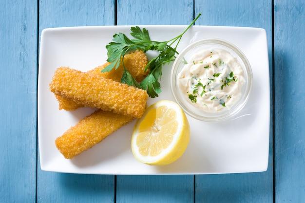 シャキッとした揚げ魚の指、レモンとブルーの木製テーブルのソース