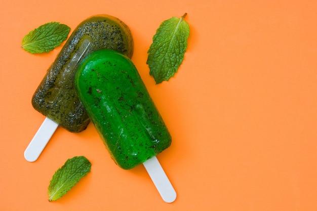 オレンジ色のテーブル上面に緑の冷凍アイスキャンディー