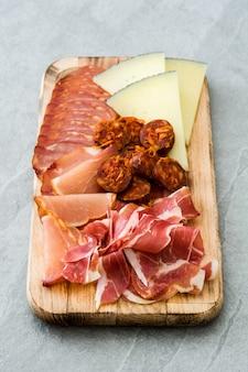 スペインのコールドカットエンブティドスチーズ、ソーセージ、ハムに灰色の石