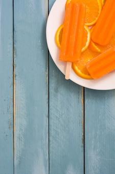 青い木製テーブルトップビューでオレンジのアイスキャンデー