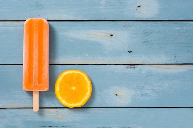 青い木製のテーブルにオレンジのアイスキャンデー