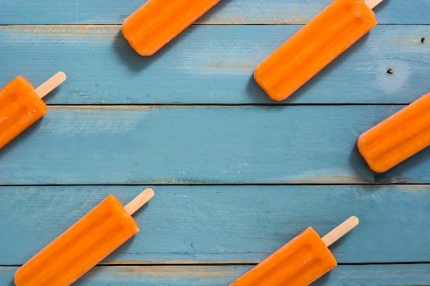 青い木製テーブルトップビューでオレンジのアイスキャンデーパターン