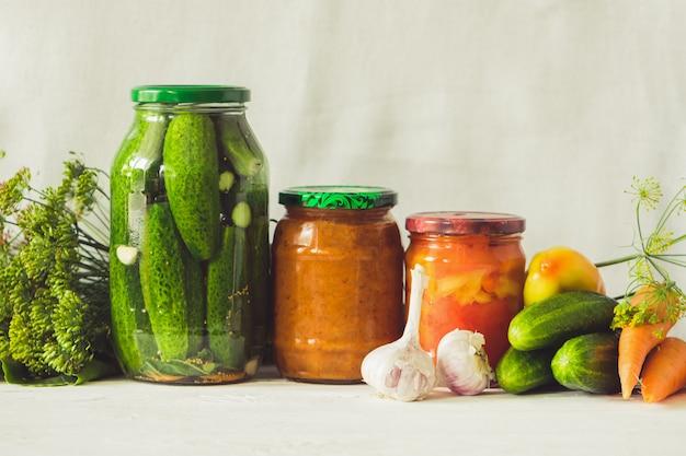 Ферментированные консервированные или консервированные овощи из овощей, кабачки, морковь, огурцы в стеклянных банках на столе