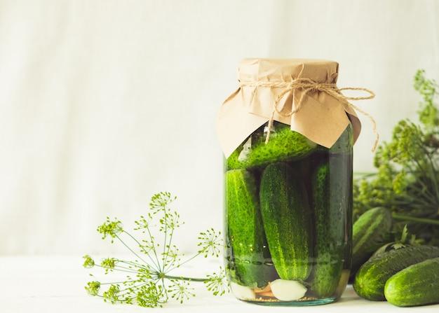 テーブルの上のガラスの瓶に発酵または缶詰のキュウリ秋の収穫の処理。缶詰食品