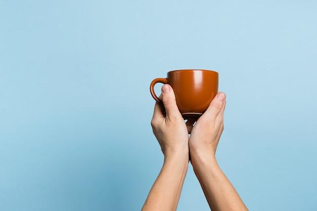 女性は彼女の手で一杯のコーヒーやお茶を保持しています。
