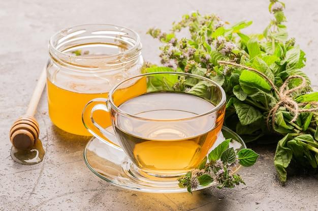 新鮮な葉と蜂蜜とお茶のカップ