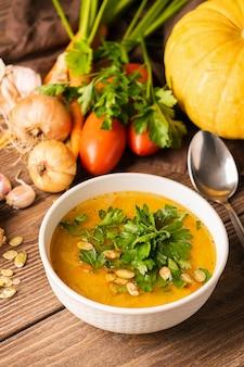 カボチャのスープと木製のテーブルでの新鮮野菜