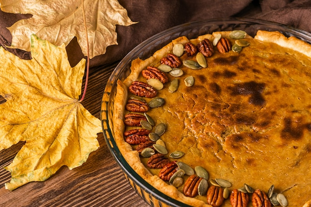 ナッツと種子で飾られた自家製の伝統的なカボチャのパイ。自然な素朴なスタイルの木製の背景。