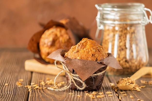茶色の紙包装のクローズアップの木製の背景で小麦フレークとマフィン。健康的なビーガンデザート。