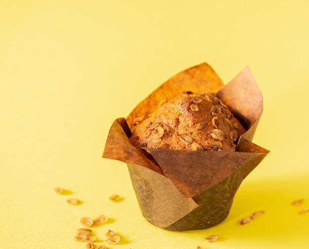 茶色の紙包装クローズアップ黄色背景の小麦フレークとマフィン。健康的なビーガンデザート。