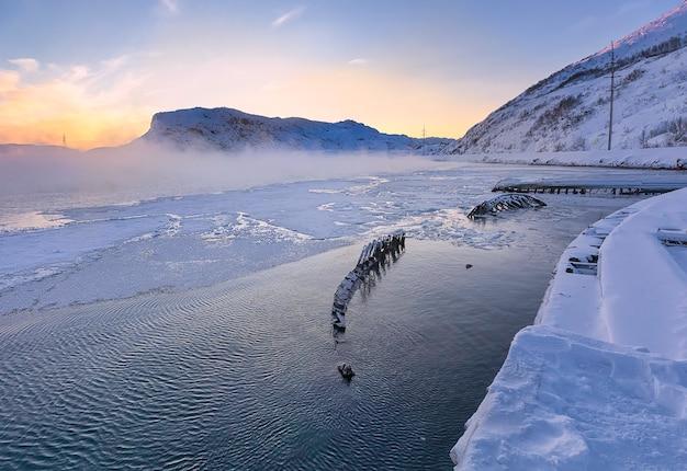 ロシアのバレンツ海の海岸線にあるテリベルカの日没時の北極圏北部の船の墓地と船の骨格