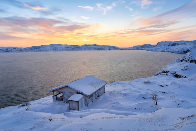 コラ半島、ムルマンスク地方、テリベルカの夕暮れ時の木造住宅とバレンツ海。ロシア