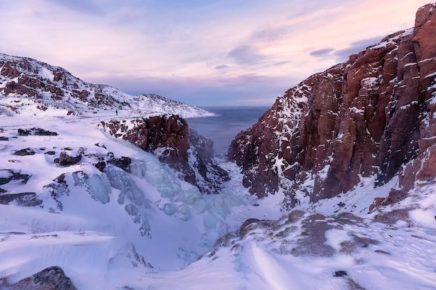 日没時の凍った滝。バレンツ海の海岸線。テリベルカ、ムルマンスク地域、コラ半島。ロシア