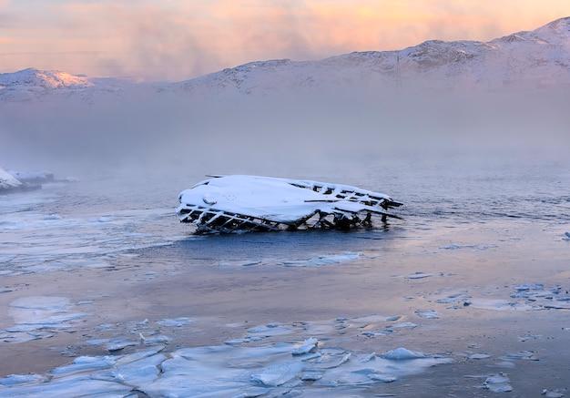 日の出のバレンツ海の海岸の古い船の帆船の金属と木製の部分。コラ半島テリベルカ。ロシア。