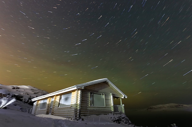 木造住宅とロシアのムルマンスク地方のバレンツ海テリベルカ上の星とオーロラの痕跡