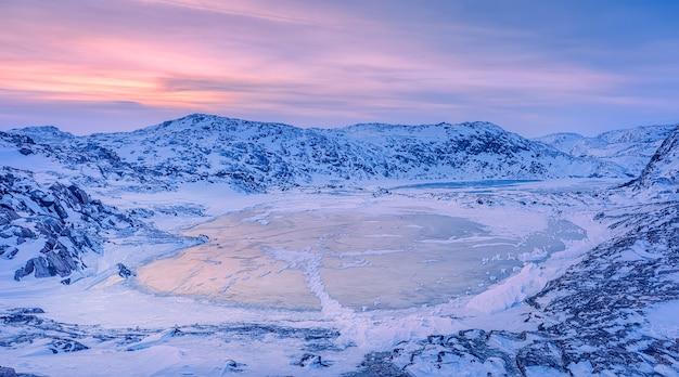 夕暮れ時の凍った湖の写真を閉じます。バレンツ海の海岸線。テリベルカ、ムルマンスク地域、コラ半島。ロシア