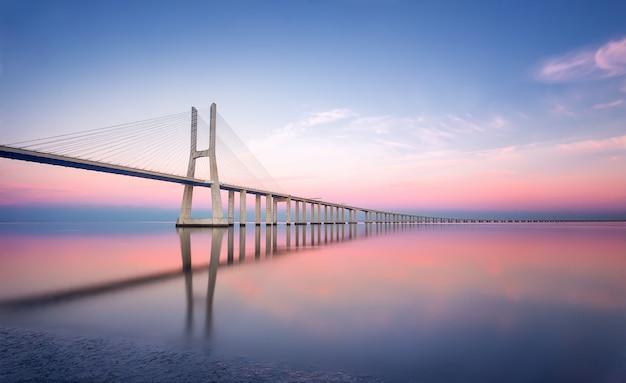 Португалия, лиссабон - васко да гама мост в лиссабоне на закате. европа. съемка с большой выдержкой