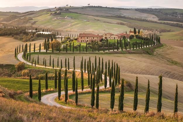 Общая итальянская деревня. фермерский дом и удивительные поля недалеко от валь д'орча. тоскана. сиена. италия. европа