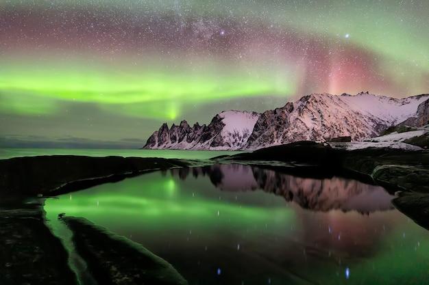 Северное сияние над пляжем эрсфьорд. остров сеня в ночное время, европа остров сеня в регионе тромс на севере норвегии. съемка с большой выдержкой.