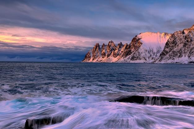 Пляж эрсфьорд на закате. остров сеня в сумерках, европа остров сеня в регионе тромс на севере норвегии. съемка с большой выдержкой.