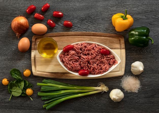 木製の背景に小さなトマト、ほうれん草、ニンニク、玉ねぎの葉で牛ひき肉