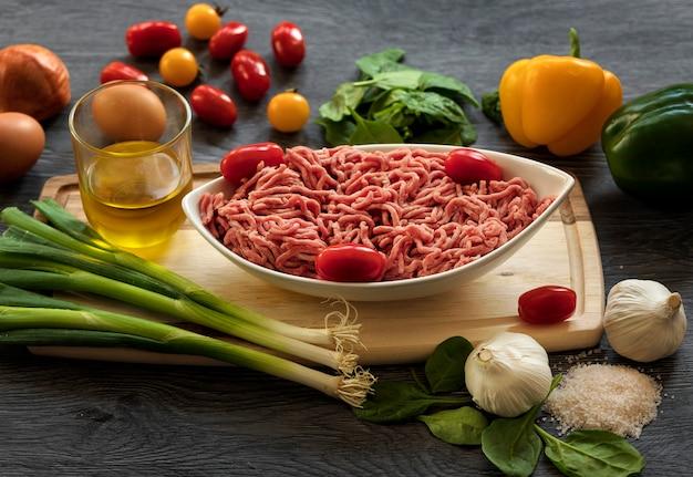 ほうれん草、トマト、ニンニク、玉ねぎと暗い背景の木の白いプレートに牛ひき肉
