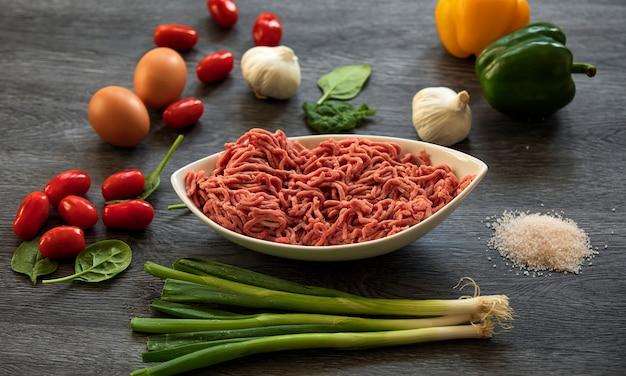 牛ミンチとほうれん草、トマト、卵、ニンニク、玉ねぎの木製の背景