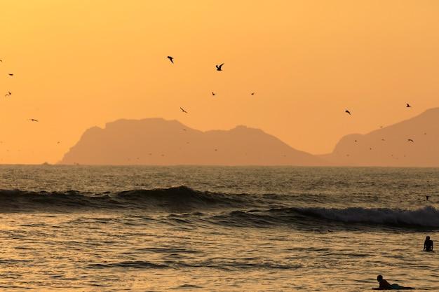 ペルーリマの太平洋のビーチでサーファーとカモメのシルエットと風光明媚な日没の瞬間