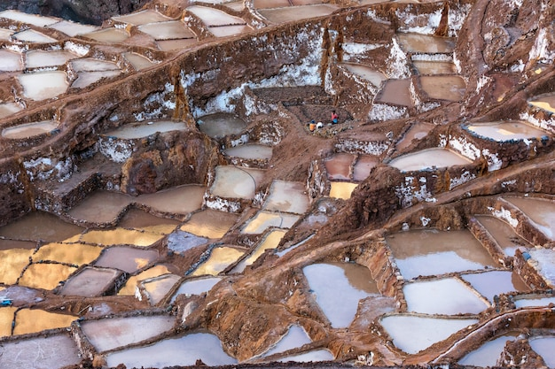 ペルーのクスコ近くのマラスの塩田の塩棚のカラフルな池の反射面を見る