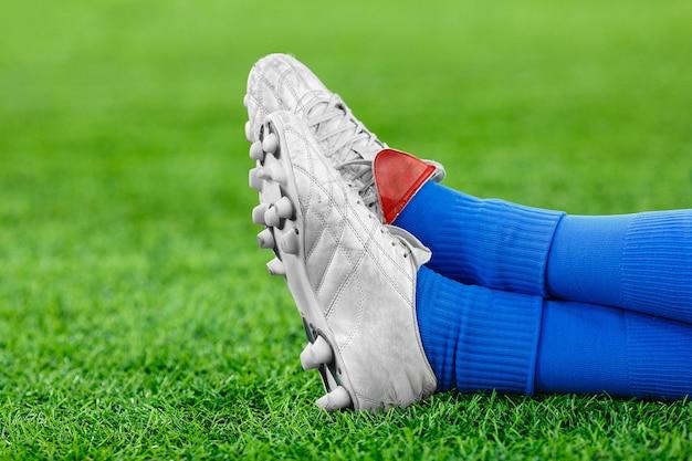 緑の芝生の上でサッカーの選手の足